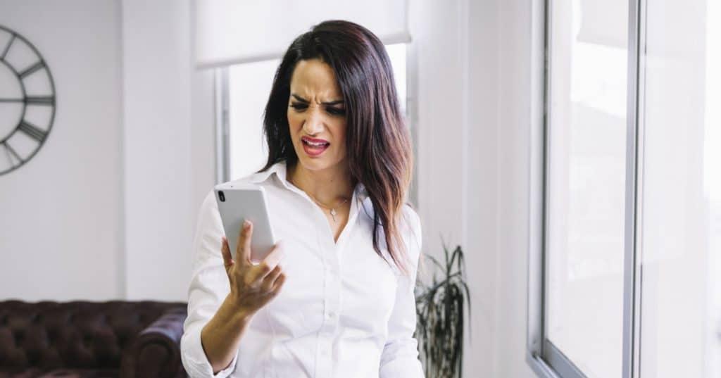 Mulher irritada olhando o celular