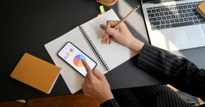 Close dos braços de uma mulher segurando um celular com gráficos e fazendo anotações em um papel no outro